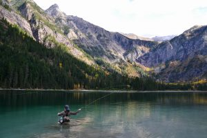 A woman fly fishes while wading in a pristine backcountry lake
