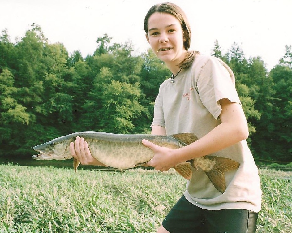 A girl holds a muskie that she caught