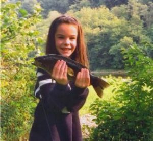 A young girl holds a smallmouth bass that she caught