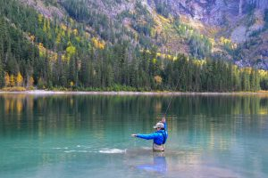 A woman catching a fish with minimal fly fishing gear in a backcountry lake