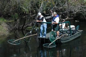 3 men in a boat use nets and electrofishing equipment to take fish samples from a river.