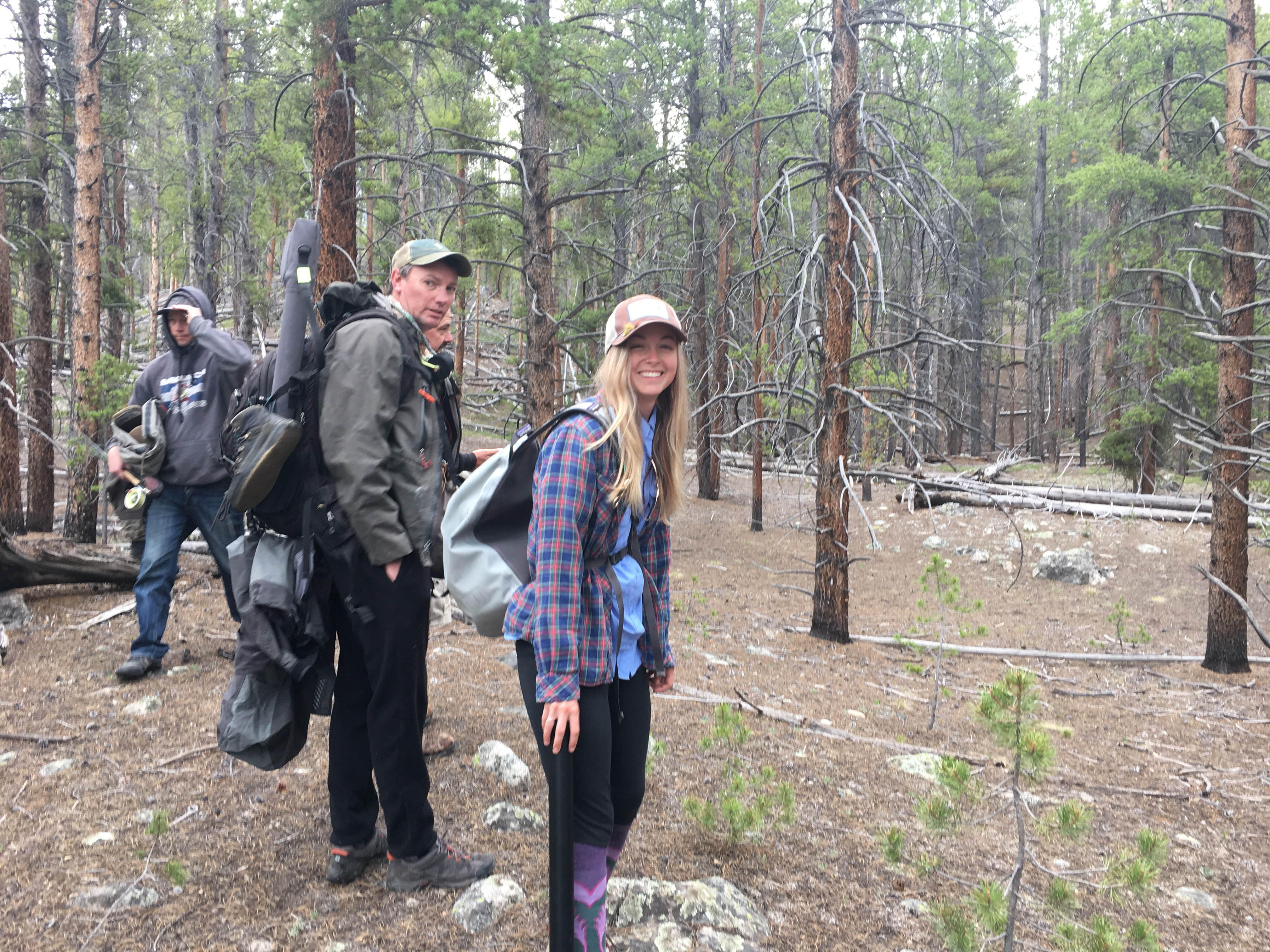 A group hiking through the woods to go fly fishing