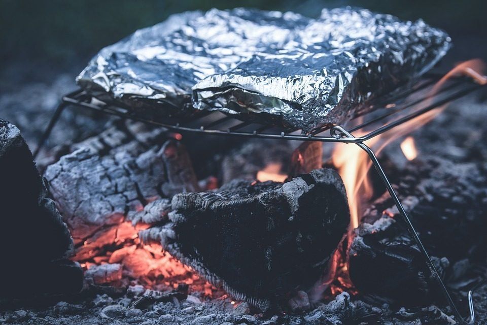 Packets of food in foil roast over a campfire