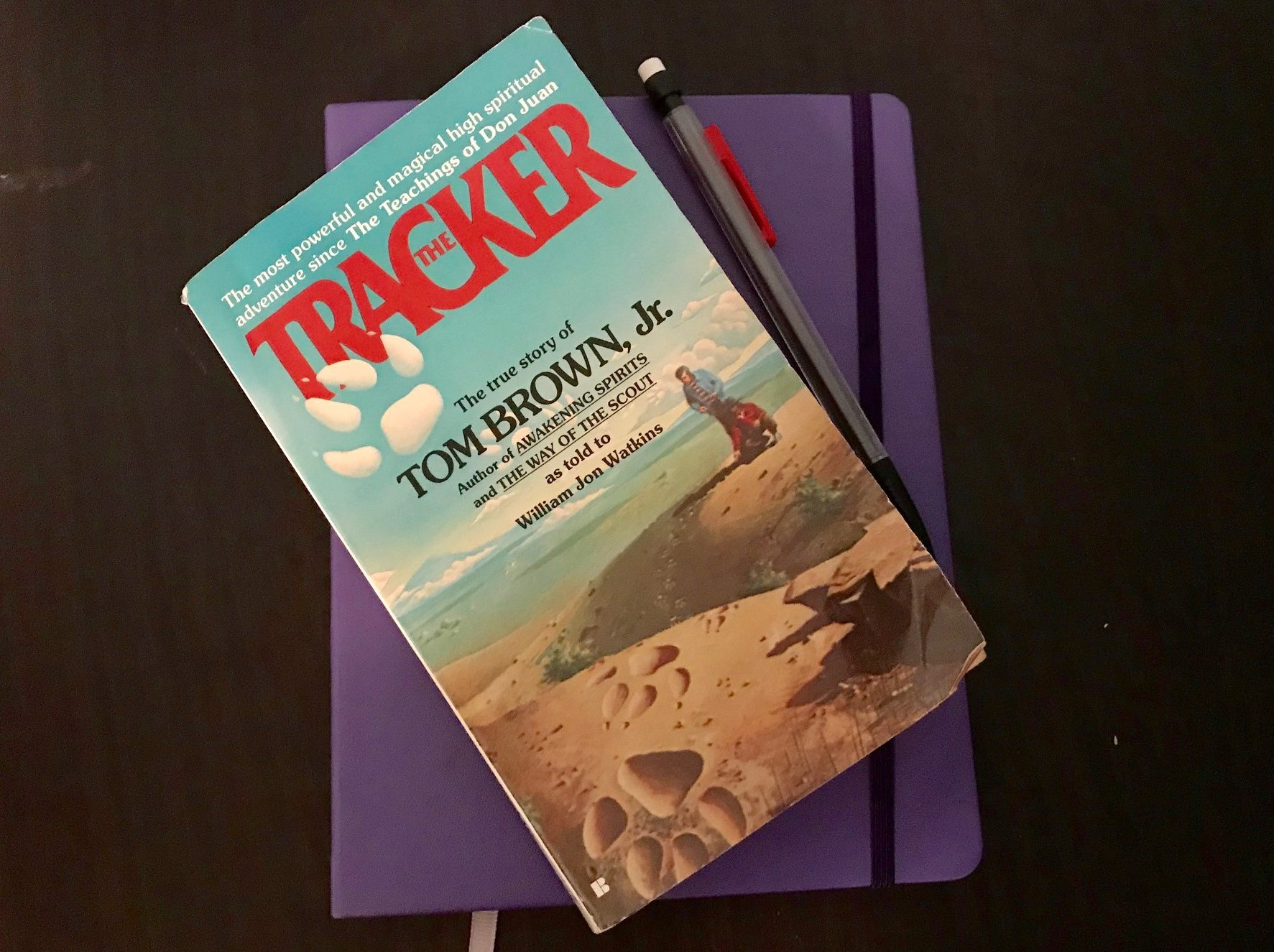 A copy of the Tracker by Tom Brown, Jr. sitting on a journal