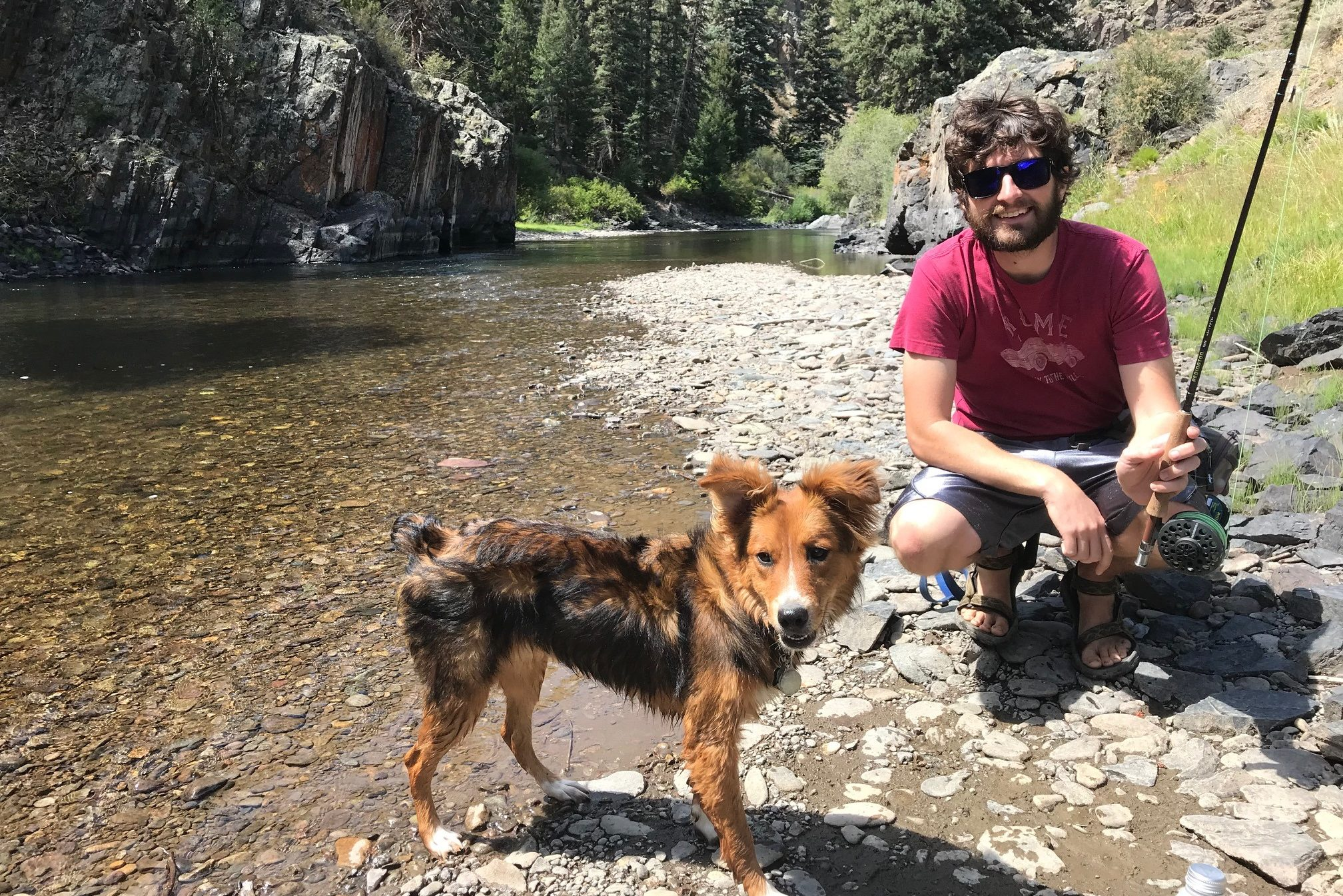 A fly fisherman and his dog pose by the river.