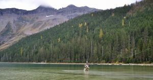 A woman fly fishes in a lake with mountains in the background.