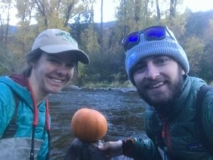 A man and woman pose in front of a pumpkin on a rock in a river.