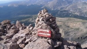 """A sign on a mountain summit reading """"Descend Keyhole Route Roll no Rocks"""""""