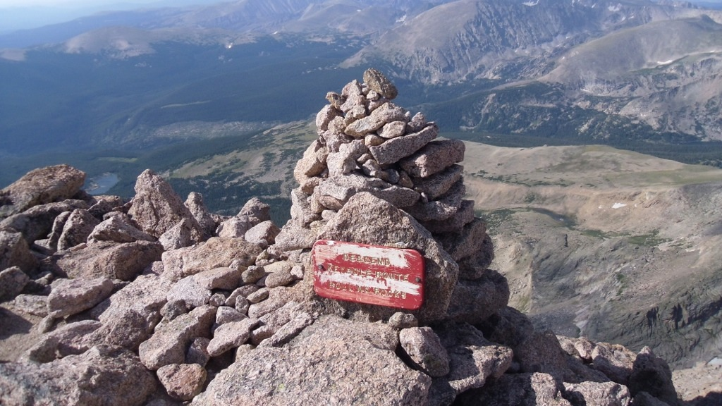 "A sign on a mountain summit reading ""Descend Keyhole Route Roll no Rocks"""