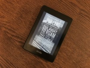 A Kindle with the cover of This Land is Our Land, sitting on a table.