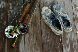 Two fly rods and a pair of shoes sitting on a wooden surface.