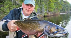 A man holds a large brook trout caught on a Canadian lake.