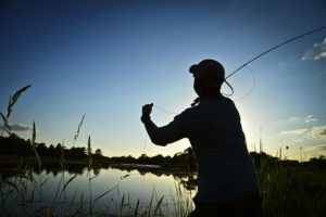 A man in silhouette casts a fly rod in a lake.