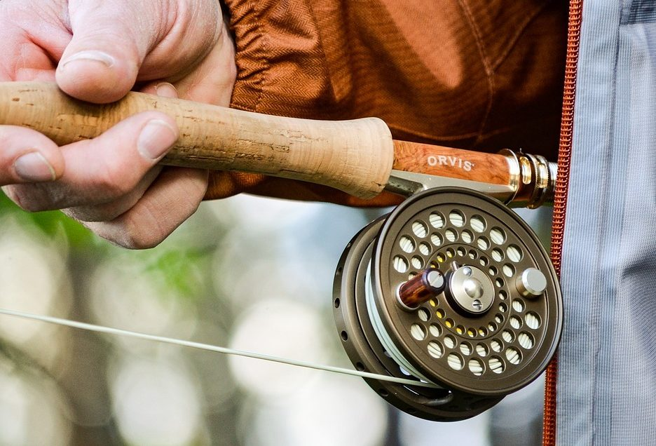 A man's hand holding a fly rod and reel