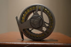 A fly reel sitting on a table.