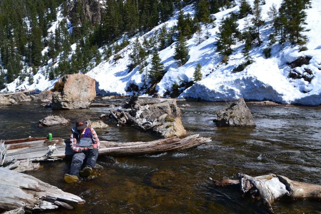 A woman sits in a river with snow in the background and writes in a journal