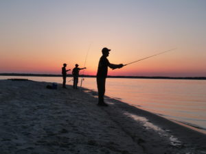 3 people fishing from shore with a sunset.