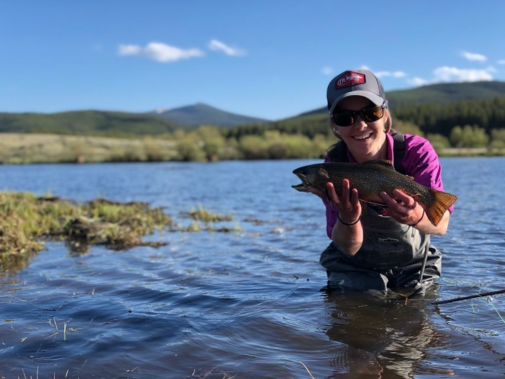 A woman kneels in a lake holding a large brook trout.