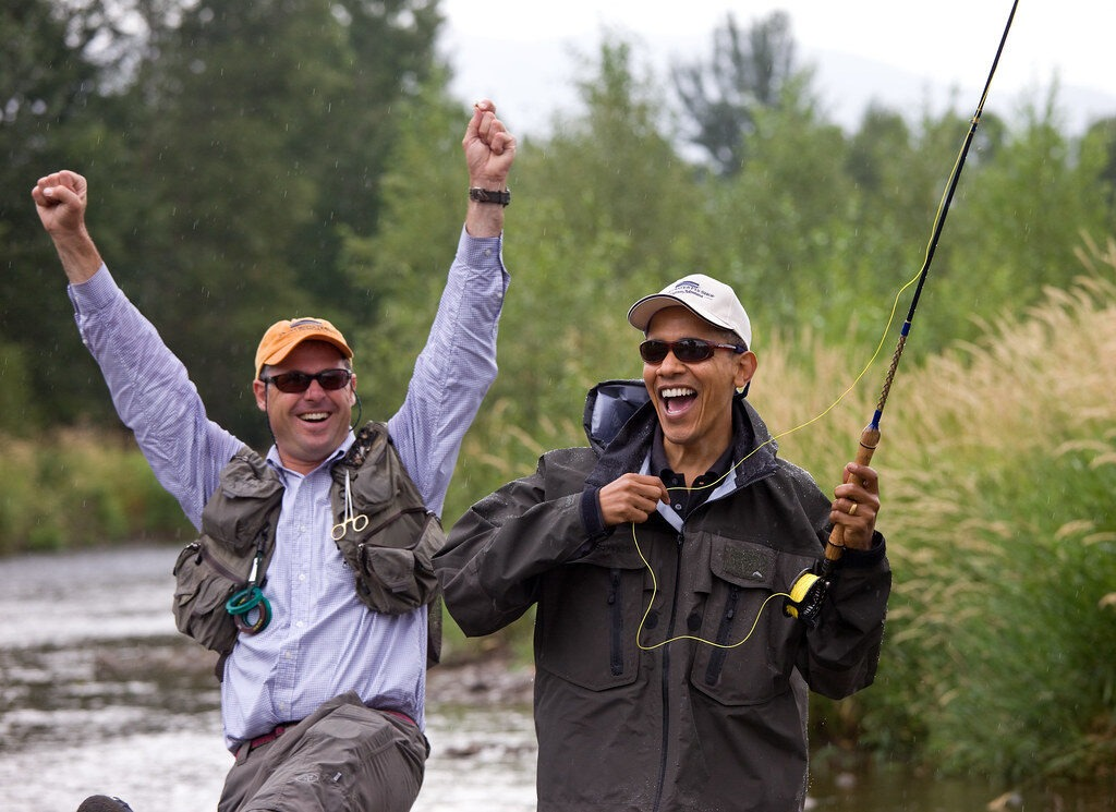 Barack Obama fly fishes on a guided trip. Both he and the guide are excited, and the guide has his hands in the air.