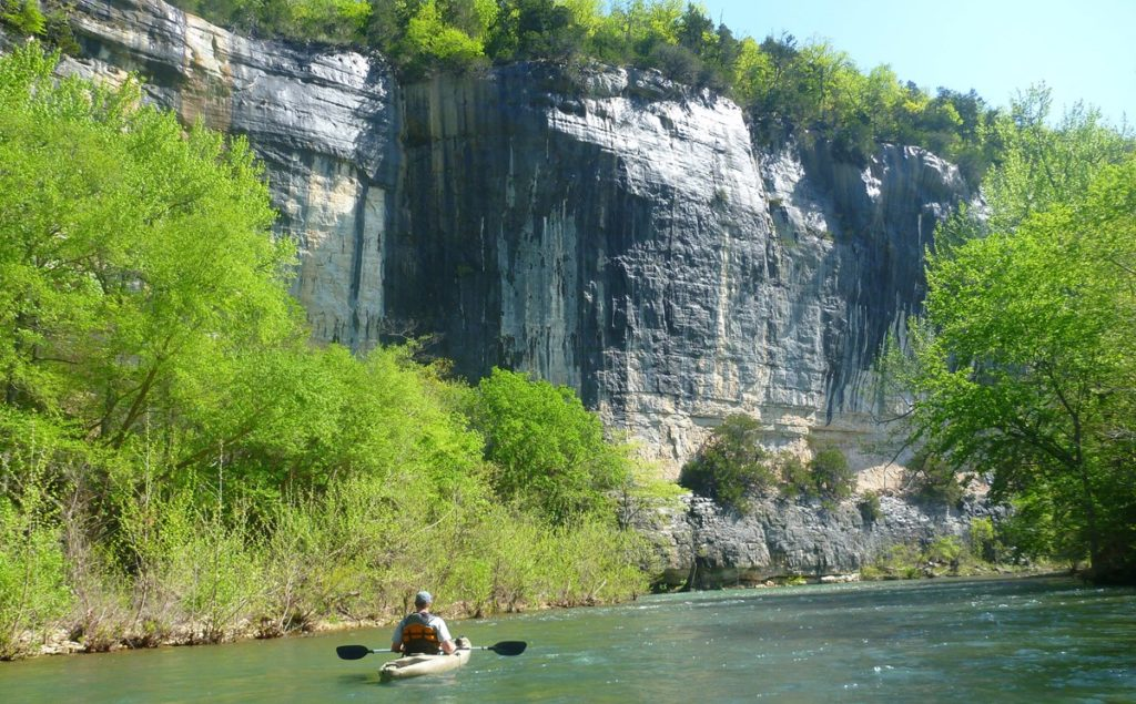 A kayaker floats down a river with trees and sheer cliffs on the left.