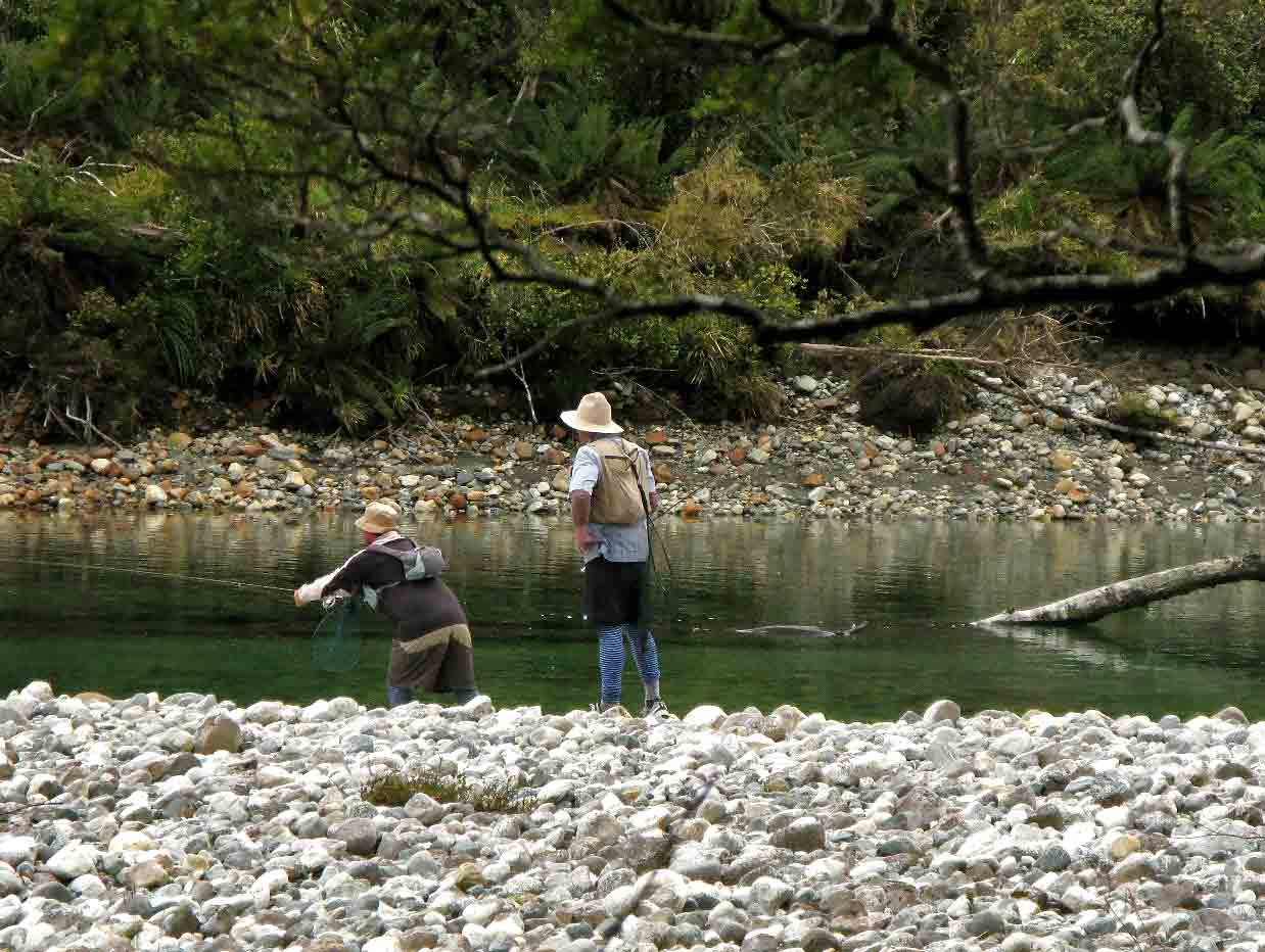 A guide helps a client fly fish on a river.