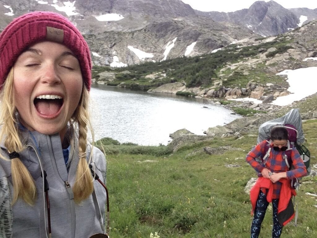 2 women gear up after a backpacking trip. One is holding the camera and making a funny face while the other gets clipped up.