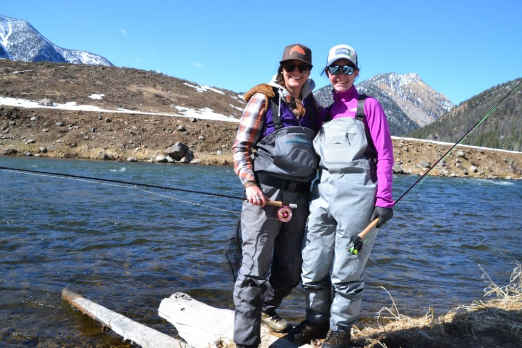 Two women pose in front of a backcountry river holding fly rods.