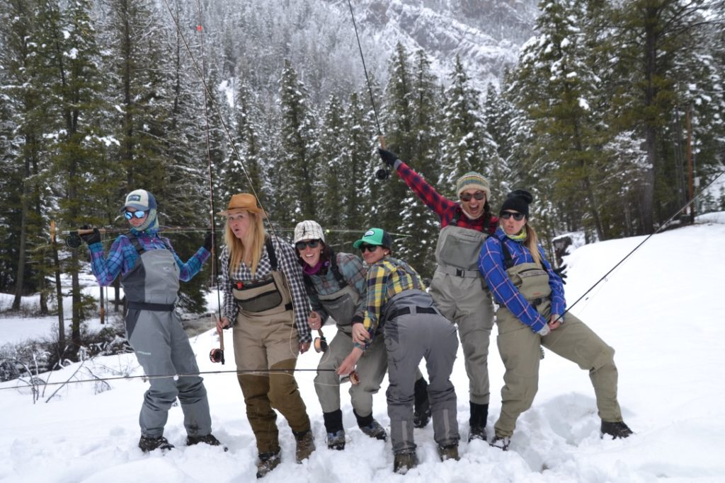 Six women pose in the snow holding fly rods and making goofy expressions.