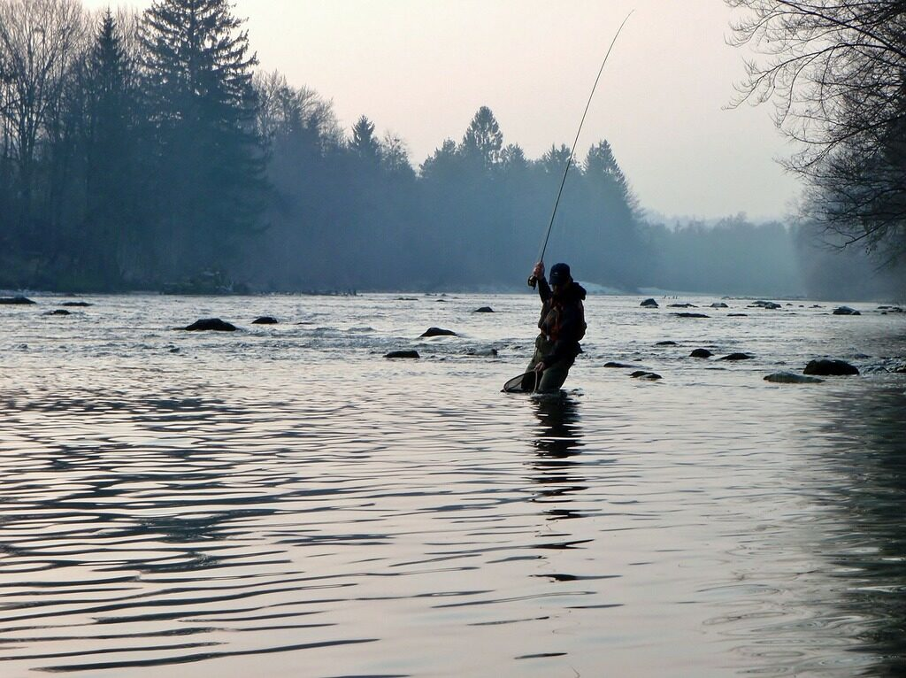 A man in silhouette fly fishes on a river with trees in the background
