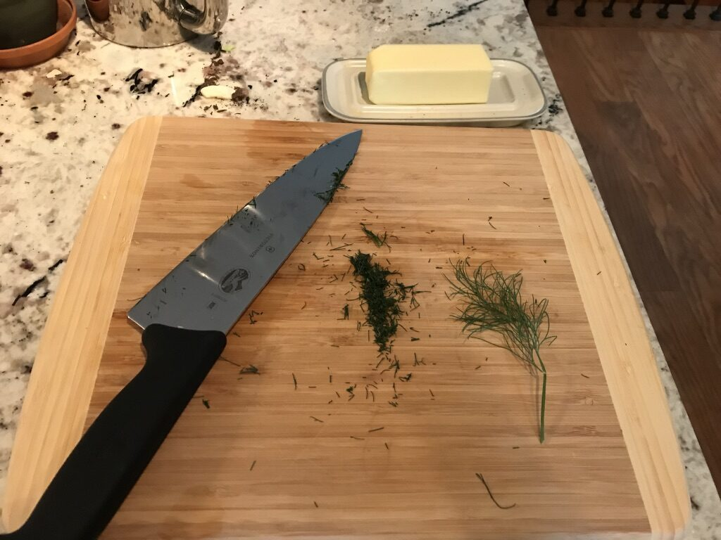 Chopped dill and butter on a cutting board near a knife