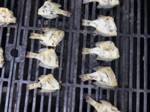 Multiple bluegills cooking on a grill