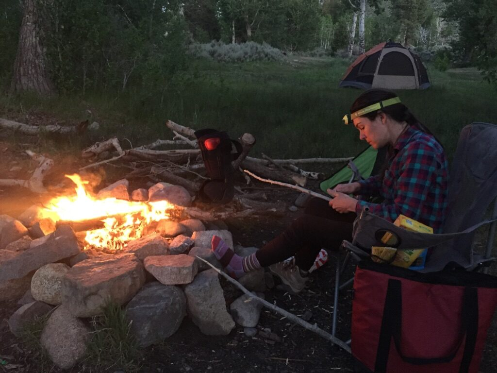 A woman sits next to a campfire and carves a stick wearing a headlamp.