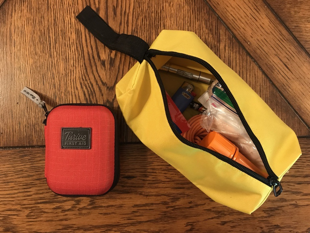 A first aid kit next to a canvas bag