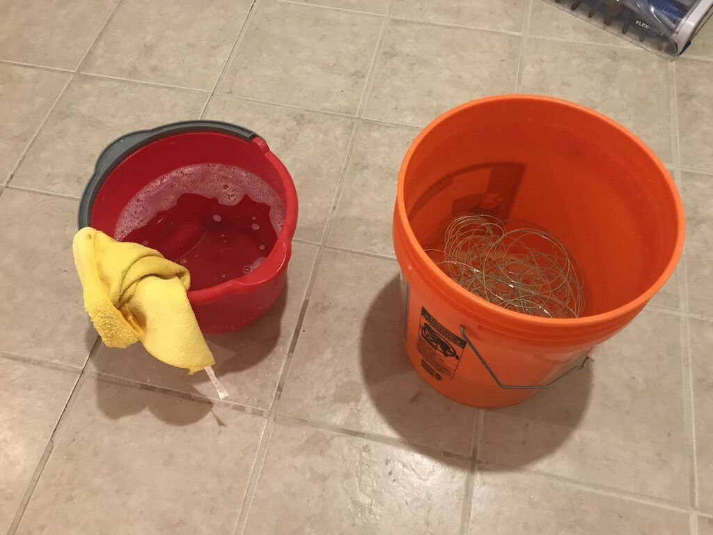 2 buckets of water on the ground. One has fly line in it and the other has a rag.