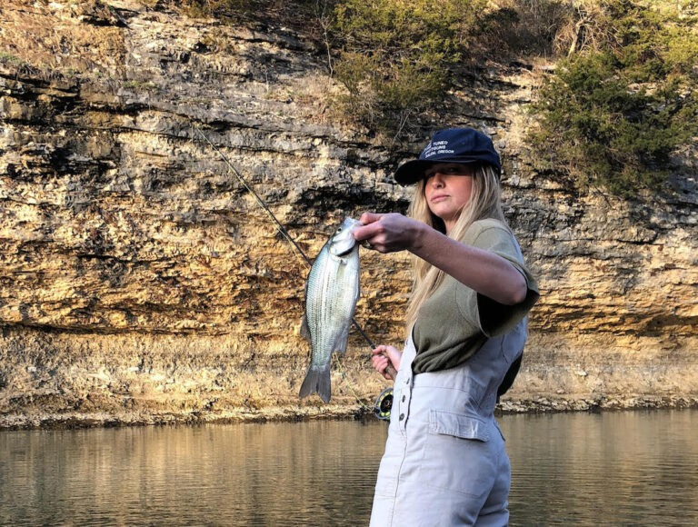 A woman holds a white bass