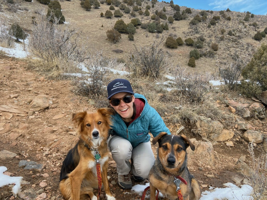 A woman on a hike poses with two dogs