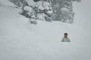 A woman in ski gear stands in deep snow