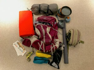 A backpack and other camping gear sitting on the floor