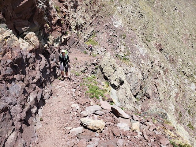Two hikers ascend along a narrow trail with cliffs to the right.