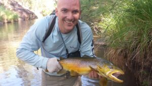 A man holds a large brown trout and smiles at the camera
