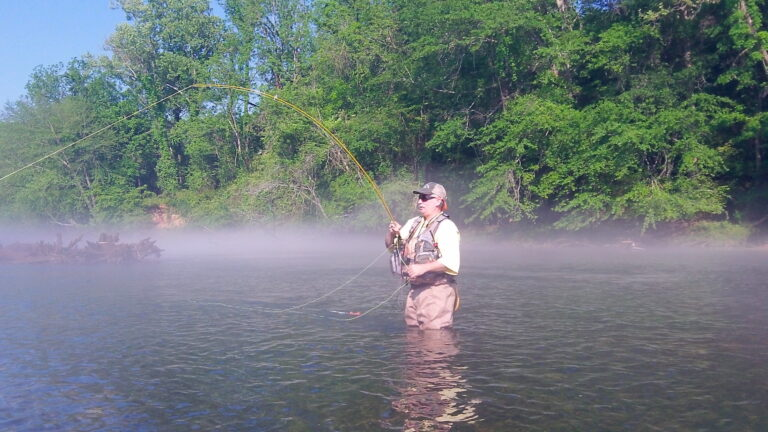 Steve Angell casts a fly rod while standing in a river