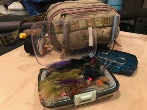 A fishing pack and fly box sitting on a wooden floor