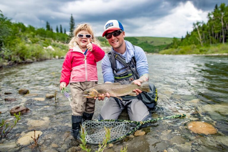Tim and Wren Hepworth kneel in a river, proudly displaying a trout they caught