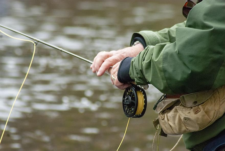 A close up shot of a man holding a fly rod/