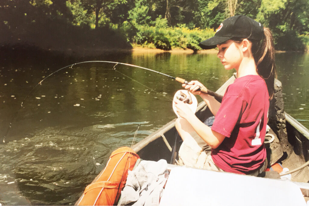 A girl sits in a boat and reels in a fish.
