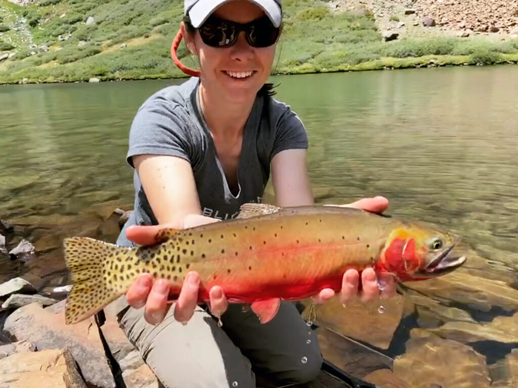 A woman kneels on a rocky shore holding a cutthroat trout.