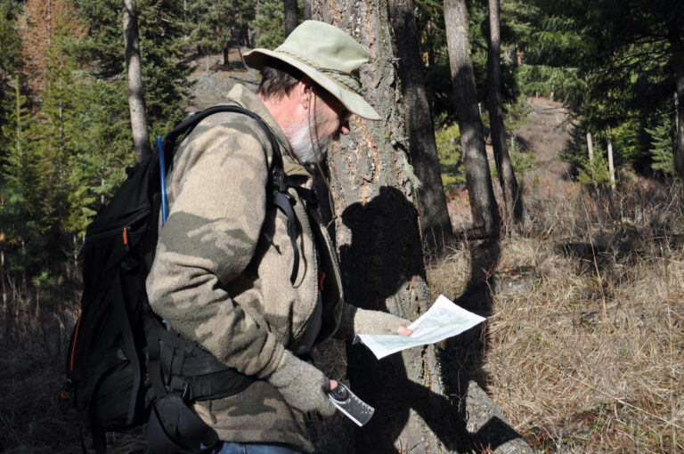 A man looks down at a map in the woods