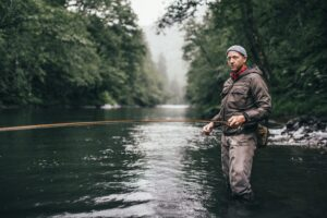 Bucky Buchstaber stands in a river with a fly rod