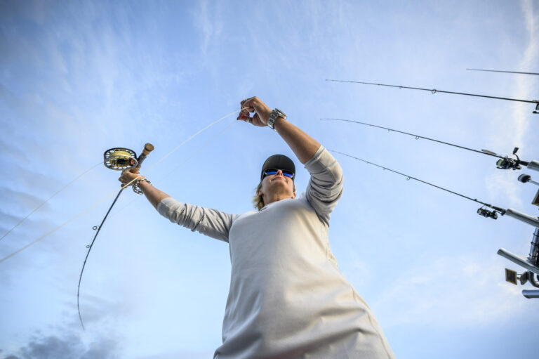 A woman casts a fly rod as the camera captures from below.