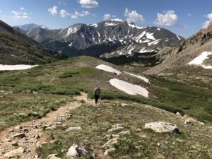 Jon Hill hiking in rugged terrain with mountains in the background